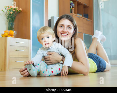 happy long-haired mom and child on wooden floor in home - Stock Photo