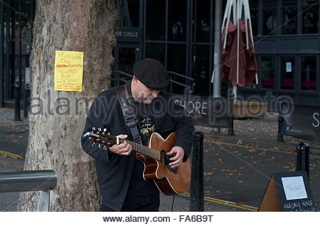Busker playing guitar - Stock Photo