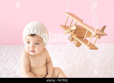 Cute toddler playing with a wooden plane - Stockfoto
