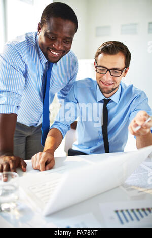Two handsome businessmen working together on a project sitting at a table in the office - Stock Photo