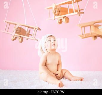 Little girl playing wooden toy planes - Stock Photo