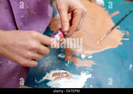 Artist's hands close-up on the background of palette - Stockfoto