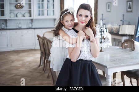 Mother and daughter relaxing in a stylish interior - Stock Photo