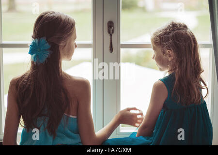 Two cute sisters looking behind the window - Stock Photo