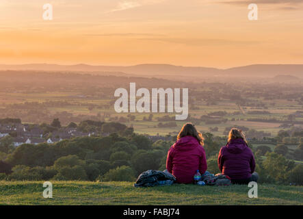 Two ladies sit on the top of Glastonbury Tor, looking out over the Somerset Levels and the Vale of Avalon watching - Stock Photo