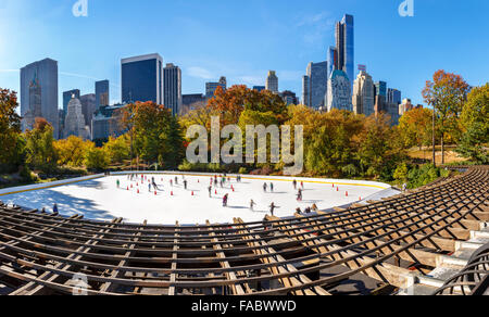 Wollman Skating Rink on a sunny morning in autumn, Central Park South and Midtown Manhattan skyscrapers. New York - Stock Photo
