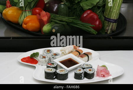 Sashimi or Sushi is a Japanese dish consisting of small balls or rolls of vinegar-flavoured cold rice served with - Stock Photo