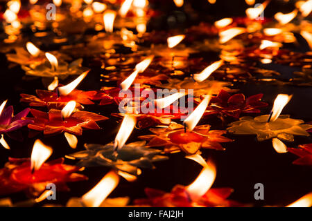 Close focus onto bright candle floating on pool of hot oil in public temple - Stock Photo