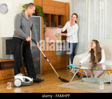 Happy family of three cleaning with vacuum cleaner in home for All in the family living room