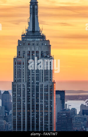 Aerial view of the top of the Empire State Building skyscraper at sunset with a fiery sky. Midtown, Manhattan, New - Stock Photo