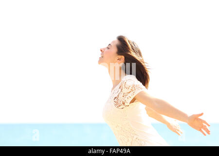 Happy woman enjoying the wind and breathing fresh air on the beach in a sunny and windy day - Stockfoto