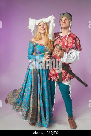 Humorous studio shot of a couple dressed as in medieval clothing posing as drunk with vine cups on purple background - Stockfoto