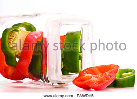 Sliced red and green peppers in jar against white background - Stockfoto
