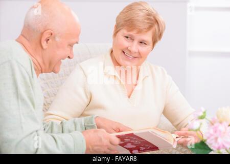 Pleasant couple looking through photo album - Stock Photo