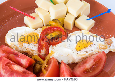 Cuban breakfast : Egg,cheese cubes with heart shaped toothpicks and tomatoes with black pepper sprinkled served - Stock Photo