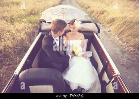 Bride and groom in a vintage car - Stockfoto