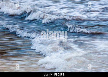 Blue foamy ocean waves breaking in shallow water, in-camera motion blur. - Stockfoto