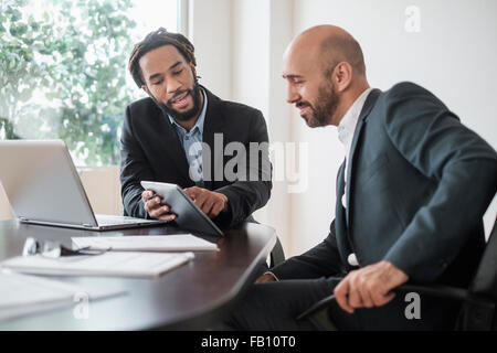 Two businessmen working with digital tablet by desk in office - Stock Photo