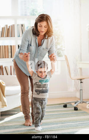 Mother holding son (2-3) making first steps - Stock Photo