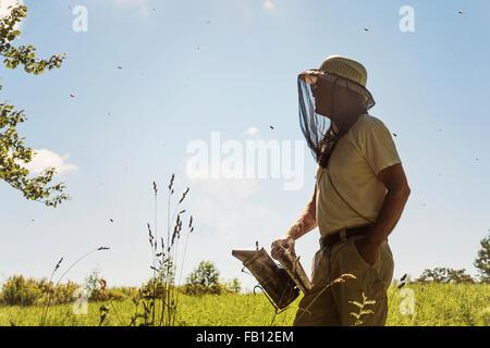 Hope, Beekeeper with smoker - Stock Photo
