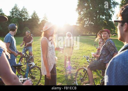 Group of party going adults arriving in park on bicycles at sunset - Stockfoto