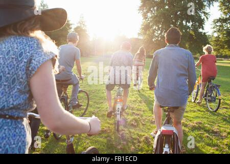 Rear view of party going adults arriving in park on bicycles at sunset - Stockfoto
