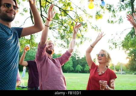 Adult friends dancing with arms raised at sunset party in park - Stock Photo