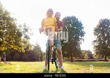 Young couple on bicycle at sunset party in park - Stock Photo