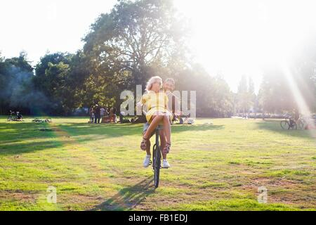 Young couple having fun on bicycle at sunset party in park - Stock Photo