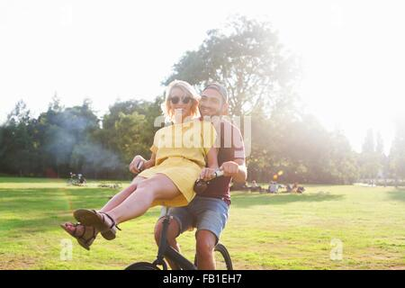Portrait of young couple having fun on bicycle at sunset party in park - Stock Photo