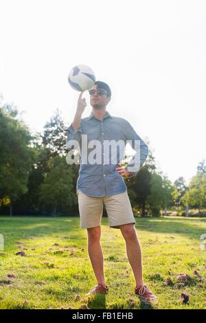 Portrait of young man on spinning a ball in sunlit park - Stock Photo
