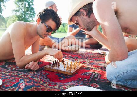 Two young men playing board game at sunset park party - Stock Photo