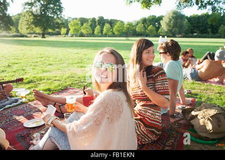 Happy young woman and friends at sunset park party - Stock Photo
