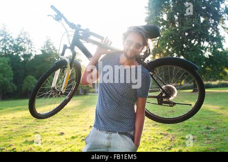 Portrait of young man carrying his bicycle in park at sunset - Stock Photo