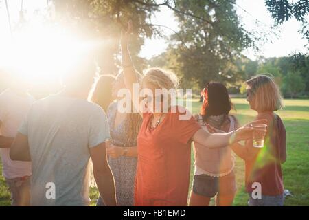 Adult friends dancing and drinking in park at sunset - Stock Photo