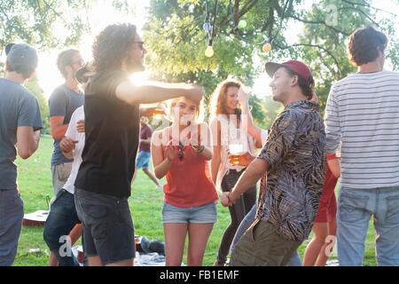 Adult friends dancing at park party at sunset - Stock Photo