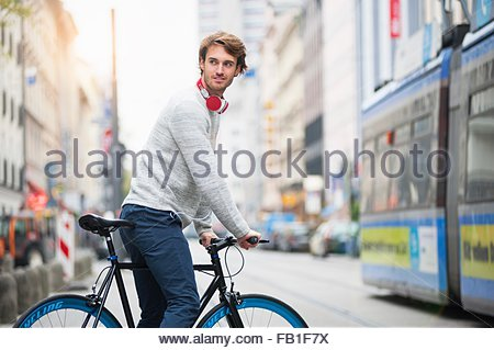Young man riding bicycle in road - Stock Photo