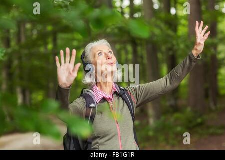 Senior woman in forest, wearing headphones, arms raised - Stock Photo
