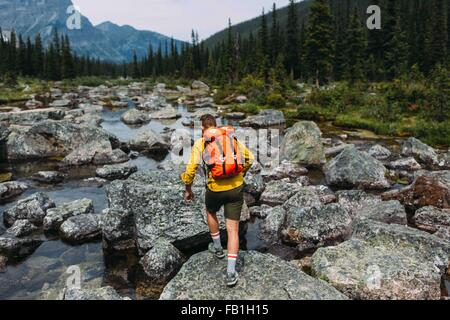 Rear view of mid adult man carrying backpack walking on rocky riverbed, Moraine lake, Banff National Park, Alberta - Stock Photo