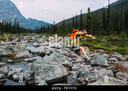 Side view of mid adult man carrying backpack jumping over rocky riverbed, Moraine lake, Banff National Park, Alberta - Stock Photo