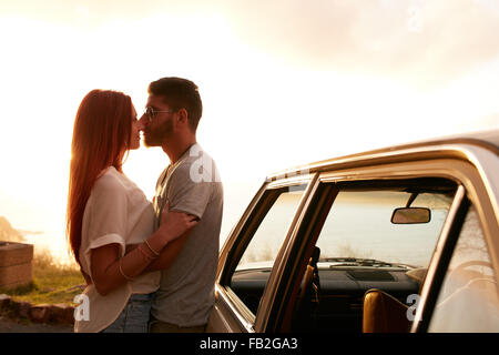 Romantic young couple standing by their car. Young man and woman about to kiss, outdoors. Enjoying summer vacation - Stock Photo