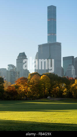 Autumn sunrise in Sheep Meadow Central Park with view on Midtown Manhattan skyscrapers, including 432 Park Avenue. - Stock Photo