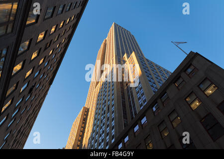Empire State Building at sunset from below. Low angle view of the Art Deco skyscraper located in Midtown Manhattan, - Stock Photo