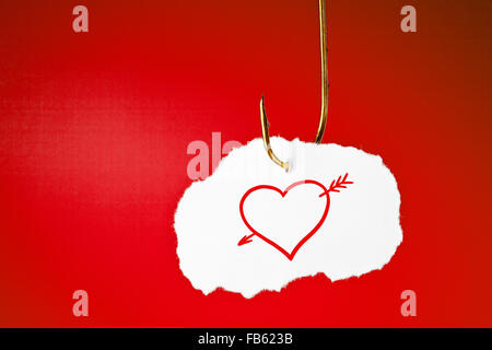 A heart pierced with an arrow drawn on white piece of paper hanging on a fishing hook over red background. - Stockfoto
