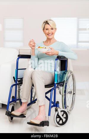 attractive senior woman on wheelchair having fruit salad - Stock Photo