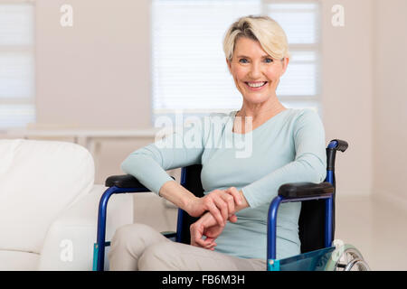 happy mid age woman sitting on wheelchair and recovering from sickness - Stock Photo