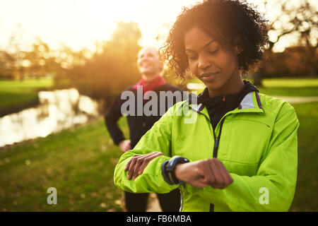Close-up of sportswoman looking at her watch, her friend on background - Stock Photo