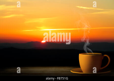 cup from coffee on a sunset - Stock Photo
