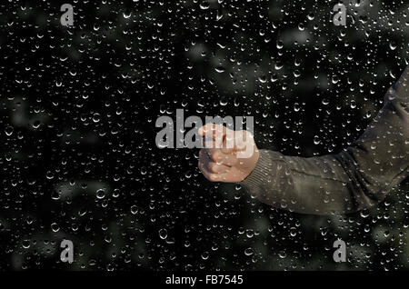 hand behind a wet window - Stock Photo