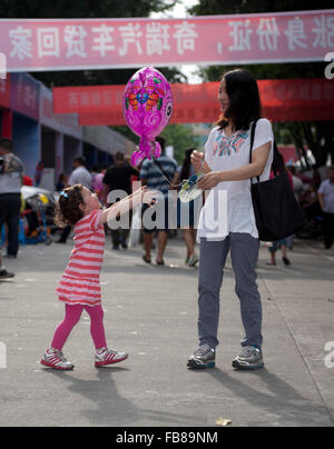 A mixed-race toddler and her Chinese mother at a trade fair in a city in China. - Stockfoto